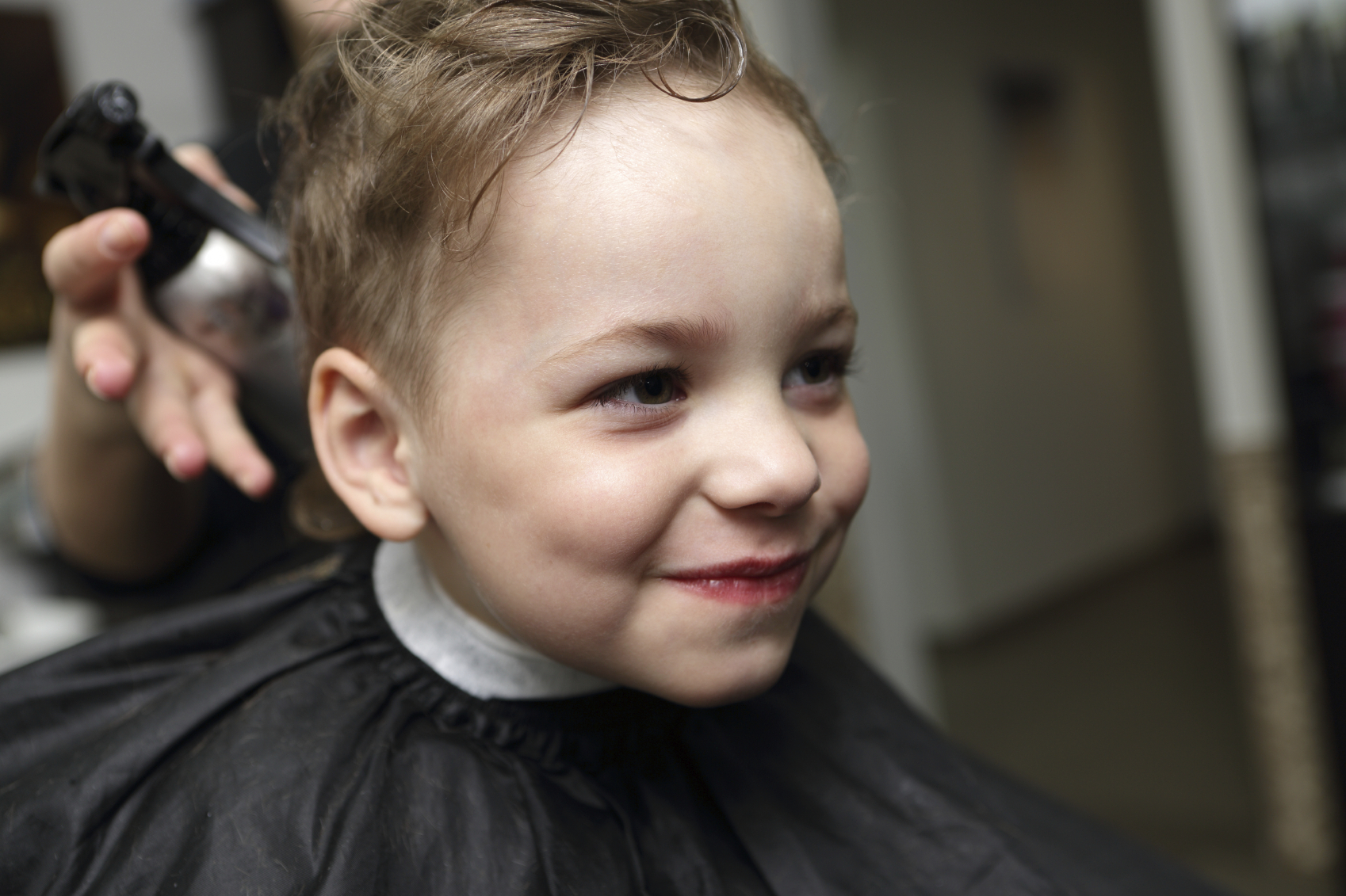 Portrait of a smiling kid at the barbershop